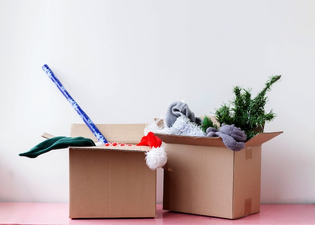 Two cardboard boxes containing an artificial christmas tree santa hat and wrapping paper.