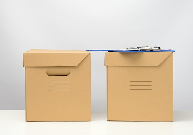 Two cardboard boxes made of brown corrugated cardboard are on a white table, moving, goods delivery