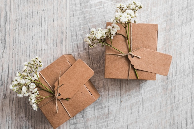 Two cardboard boxes with tag and baby's-breath flowers on wooden backdrop