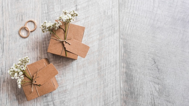 Two cardboard gift boxes with wedding rings on wooden textured backdrop