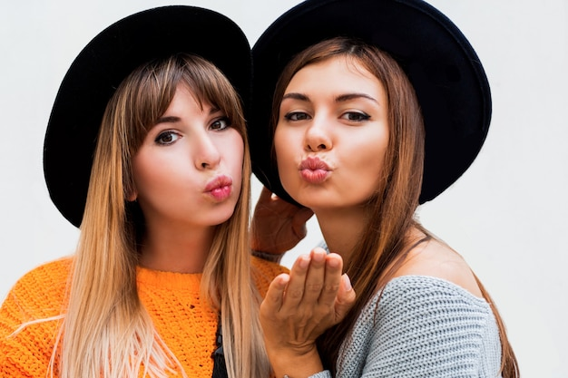 Two carefree girls sending air kiss standing on white