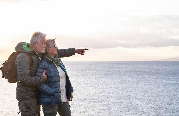 Два беззаботных пожилых человека с рюкзаком наслаждается походом на океанские скалы, глядя на горизонт