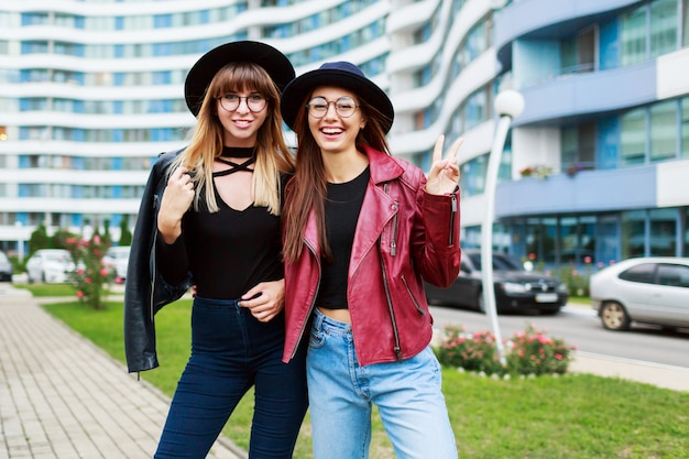 2 беззаботных усмехаясь женщины представляя на современном городе. носить шерстяную шапку, кожаную куртку и джинсы.