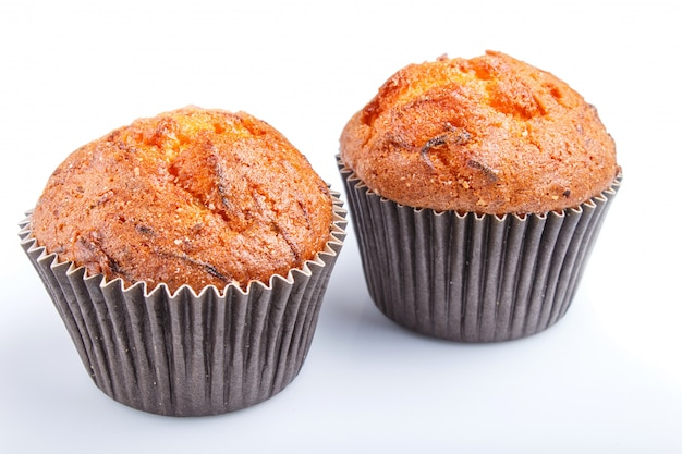 Two carrot muffins isolated on white