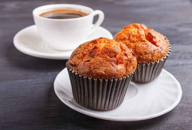 Two carrot muffins with cup of coffee on white plate on black wooden background