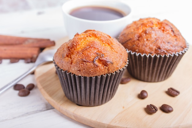 Two carrot muffins with cup of coffee on wooden kitchen board on white wooden background