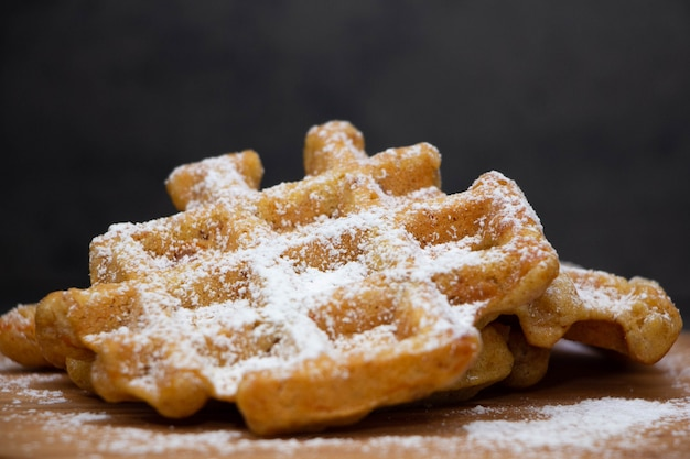 Two carrot waffles sprinkled with powdered sugar on a wooden board.