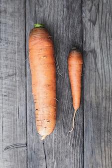 Две морковки на деревянном столе, большая и маленькая, концепция самоуважения и конкуренции