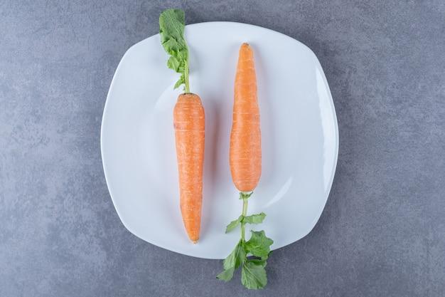 Due carote in un piatto, sulla superficie di marmo.