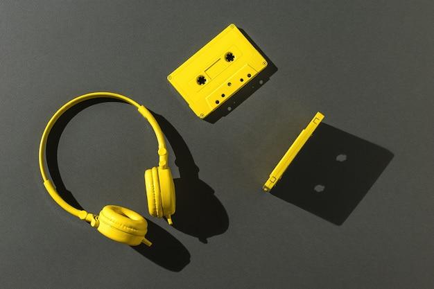 회색 배경에 밝은 빛으로 자기 테이프와 노란색 헤드폰이 있는 두 개의 카세트. 컬러 트렌드. 음악을 듣기 위한 빈티지 장비입니다. 플랫 레이.