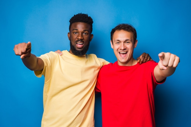 Two casual men mixed race pointed on camera isolated on blue wall