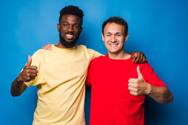 Two casual men mixed race with thumbs up isolated on blue wall