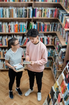 Two casual teenagers standing in college library among shelves with books and discussing home task after classes