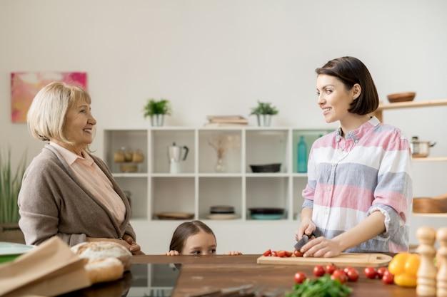Две случайные женщины разговаривают на кухне, а младшая режет овощи для салата