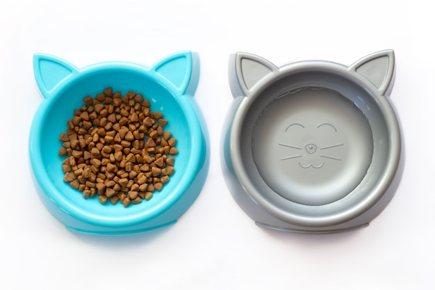 Two cat food cups in the form of cat heads isolated on a white background. blue and silver plastic bowls with dry kitten food and water