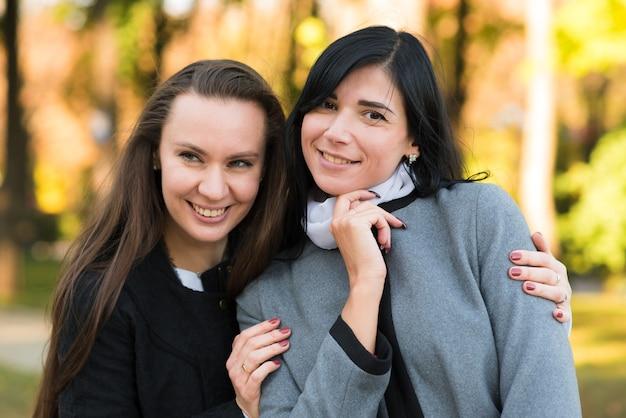 2人の白人のブルネットの女の子が日当たりの良い秋の公園で抱き締めています。幸せなレズビアンのカップル、lgbt、lgbtq。