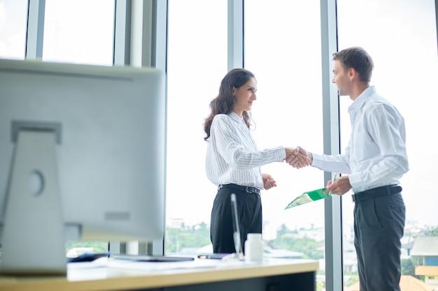 オフィスで協力のために握手する2人の白人ビジネスマン。