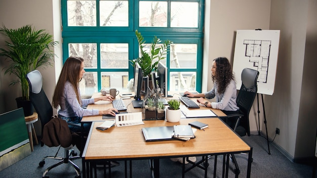 近代建築事務所での作業中にコンピューターに入力する2人の白人のビジネス女性。