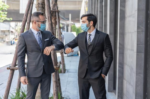 2人の白人ビジネスマンが、ストリートでのコロナウイルスcovid-19の流行中に、肘をぶつけて医療用マスクの挨拶をします。
