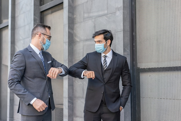 Two caucasian businessmen wear medical mask greeting with bumping elbows during coronavirus covid-19 epidemic at street
