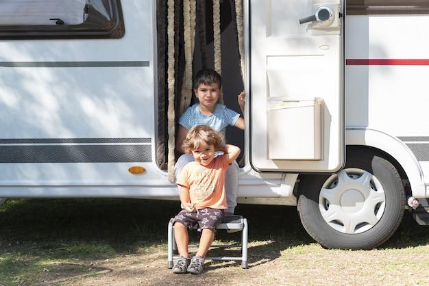 2人の白人の子供たちがキャラバンで遊んだり、別の休日を過ごしたりします