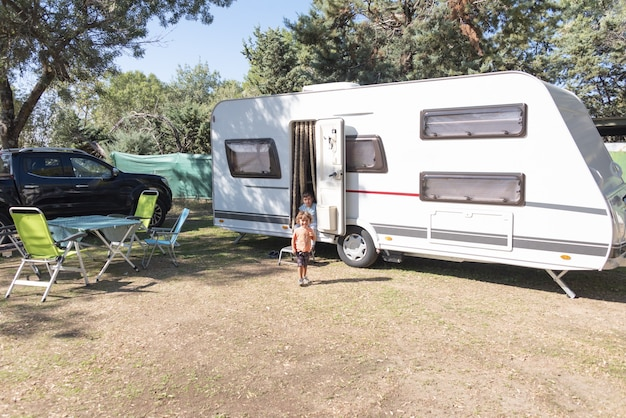 Two caucasian children play and spend alternative holidays in a caravan