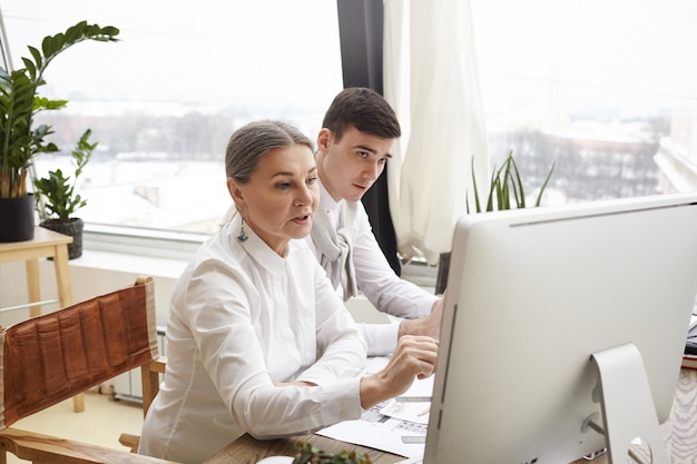 Two caucasian designers working in modern office using generic computer: stylish mature female sharing ideas on living room interior design with her handsome young coworker. teamwork and cooperation