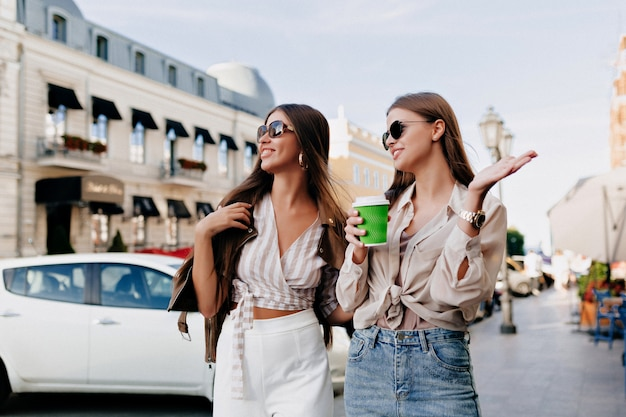 Two caucasian female friends walking together in city while drinking coffee and talking.