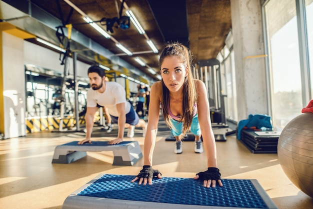 Two caucasian focused friends doing planks on steppers in a gym. selective focus on woman.