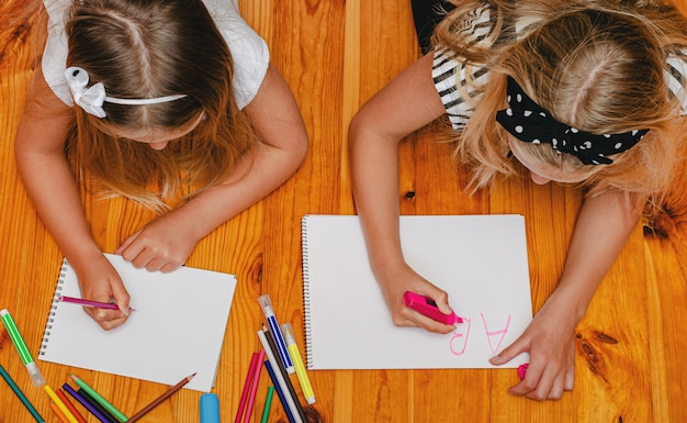 Two caucasian girls having fun on the floor, drawing and writing. overhead.