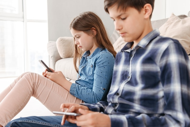 Two caucasian kids girl and boy sitting on floor near sofa at home, and both using mobile phone