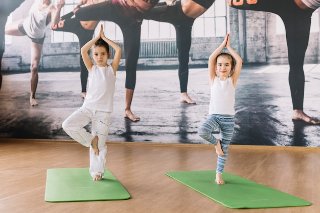 Two caucasian little girl practicing on yoga mat over wooden surface