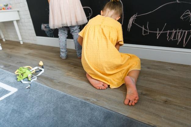 Two caucasian little girls draw on the board with chalkboard