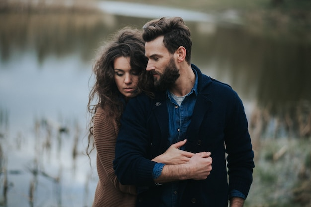 호수 근처에 두 백인 연인. 젊은 부부 는가 날 야외에서 포옹입니다. 수염 난 남자와 사랑에 곱슬 여자. 발렌타인 데이.