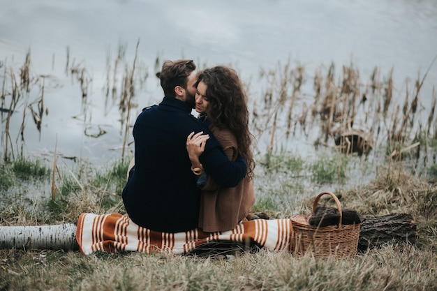Two caucasian lovers sitting on blanket by the lake. young couple is hugging on autumn day outdoors. valentine's day.