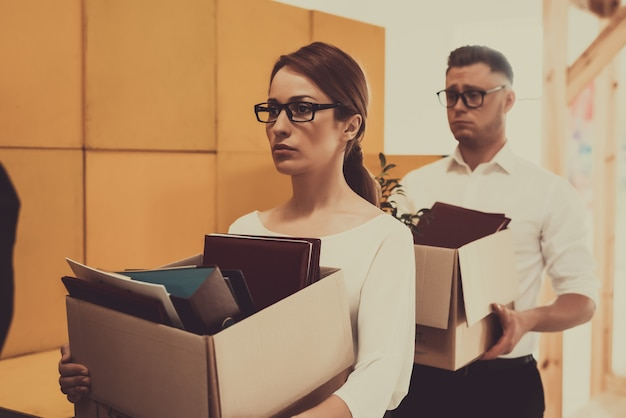 Two caucasian managers are holding office boxes.