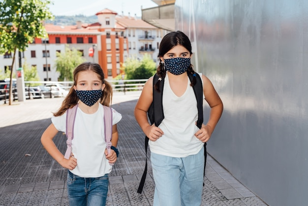 Covid19コロナウイルスのパンデミックのため、顔にマスクを付けて学校に通う、年齢の異なる2人の白人姉妹