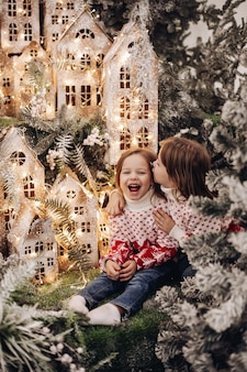 Due sorelle caucasiche posa per la fotocamera in una bellissima decorazione natalizia con molti alberi sotto la neve