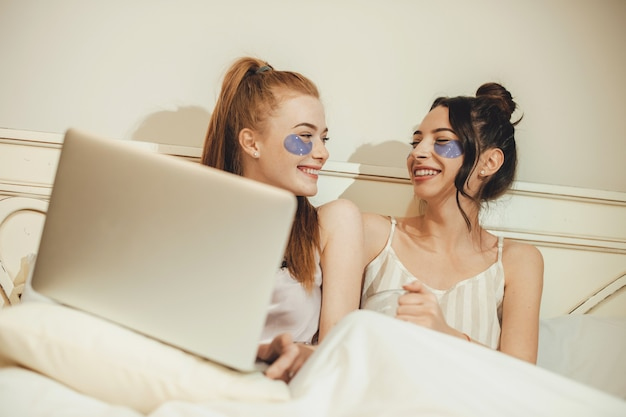 컴퓨터와 함께 침대에 누워있는 동안 노화 방지 마스크를 쓰고 두 백인 자매