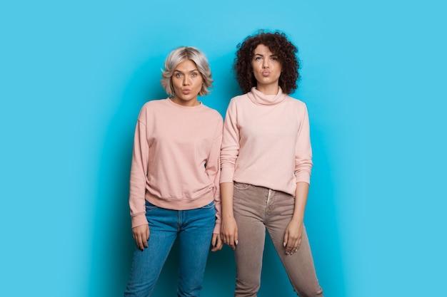 같은 스웨터를 입고 곱슬 머리를 가진 두 백인 자매가 포즈를 취하고 파란색 벽에 키스를 입술로 몸짓