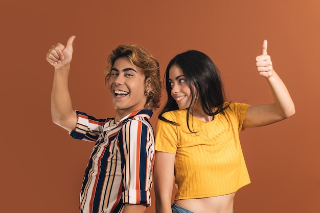Две кавказские улыбающиеся модели, блондин и брюнетка позируют с большими пальцами руки вверх перед коричневой стеной