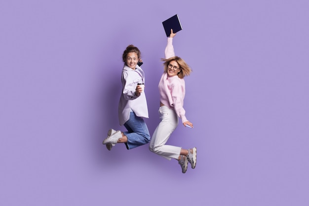캐주얼 옷을 입은 두 백인 학생은 책을 들고 카메라에 미소를 짓는 동안 보라색 스튜디오 벽에 뛰어 오르고 있습니다.