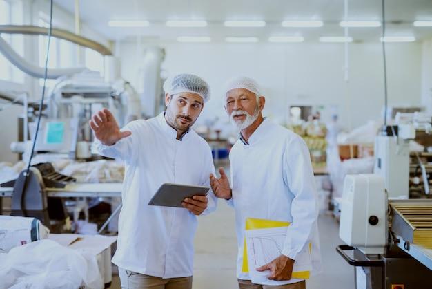 Два кавказских надсмотрщика в белой стерильной форме стоят на пищевом комбинате. младший держит планшет и показывает пальцем, а старший держит папку с документами под мышкой.