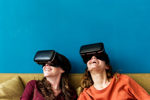 Two caucasian woman using vr on a sofa