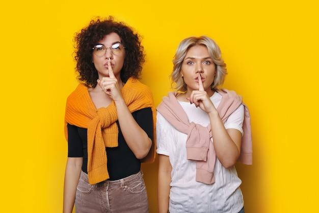 2人の白人女性が、正面を真剣に見ている空きスペースのある黄色い壁に沈黙のサインを身振りで示しています
