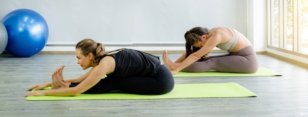 Two caucasian women exercise doing the yoga pose stretching at home