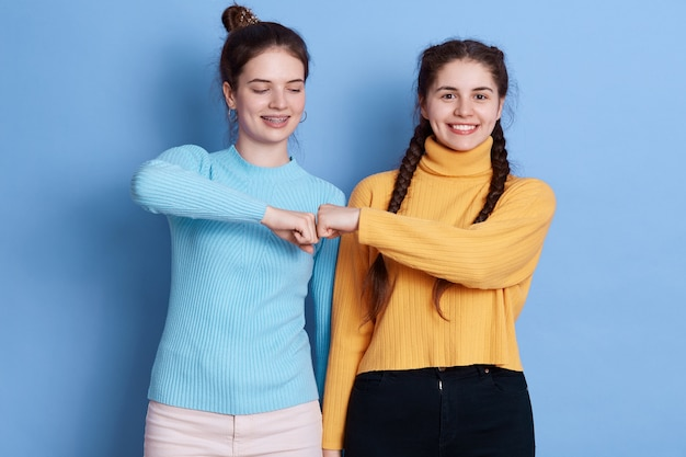 Two caucasian women fist bumping against blue wall