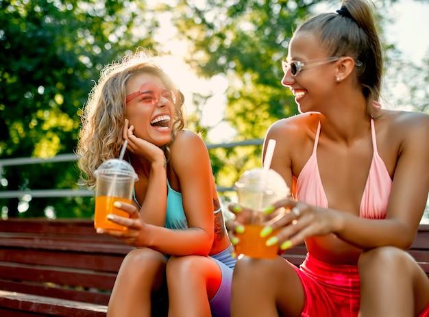 水着姿の2人の白人女性の友人は、ジュースやレモネード、ローラーブレードを飲み、スケートパークで楽しんでいます。