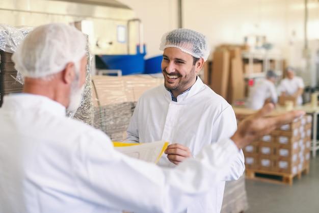 Два кавказских рабочих в защитном костюме разговаривают и улыбаются, стоя на пищевом заводе.