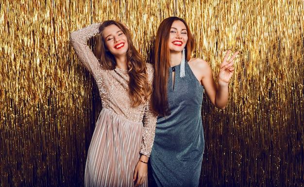 Two celebrating girls in elegant evening dress posing on golden  sequence